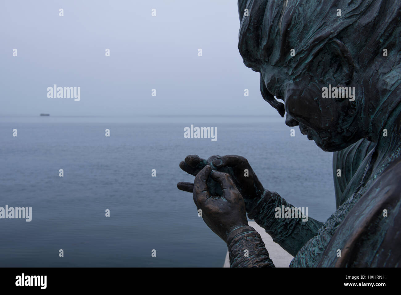 One of the two seamstresses ('Sartine') sewing on the Italian flag over the Gulf of Trieste. Sculpture by - Stock Image