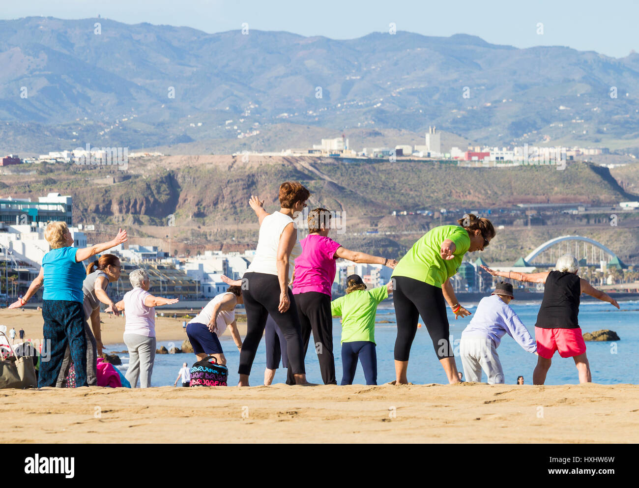 Pensioners keep fit class on beach in Spain - Stock Image