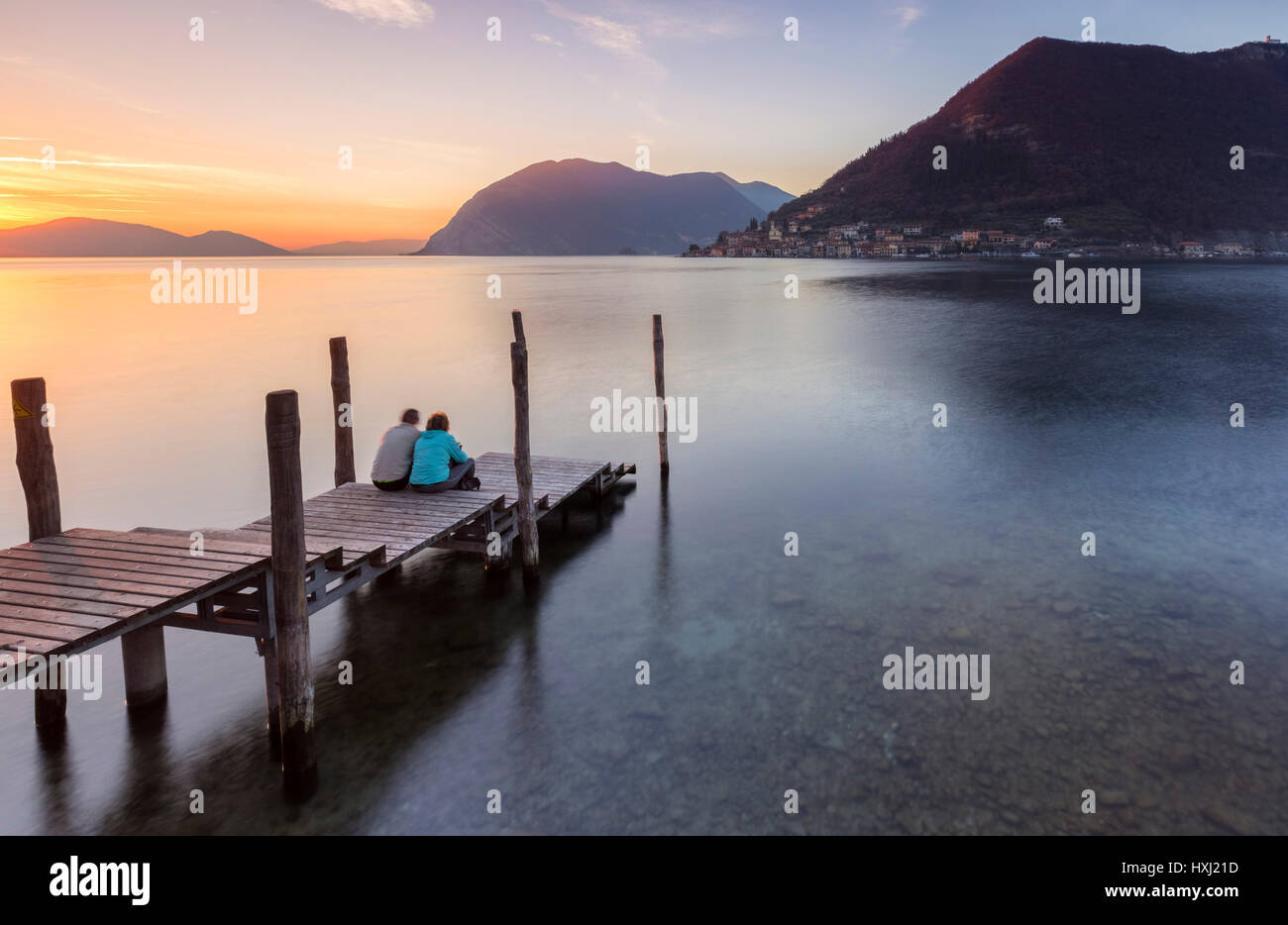 A couple on the pier of Sulzano, in front of Monte Isola, Brescia Province, Iseo Lake, Lombardy, Italy. - Stock Image
