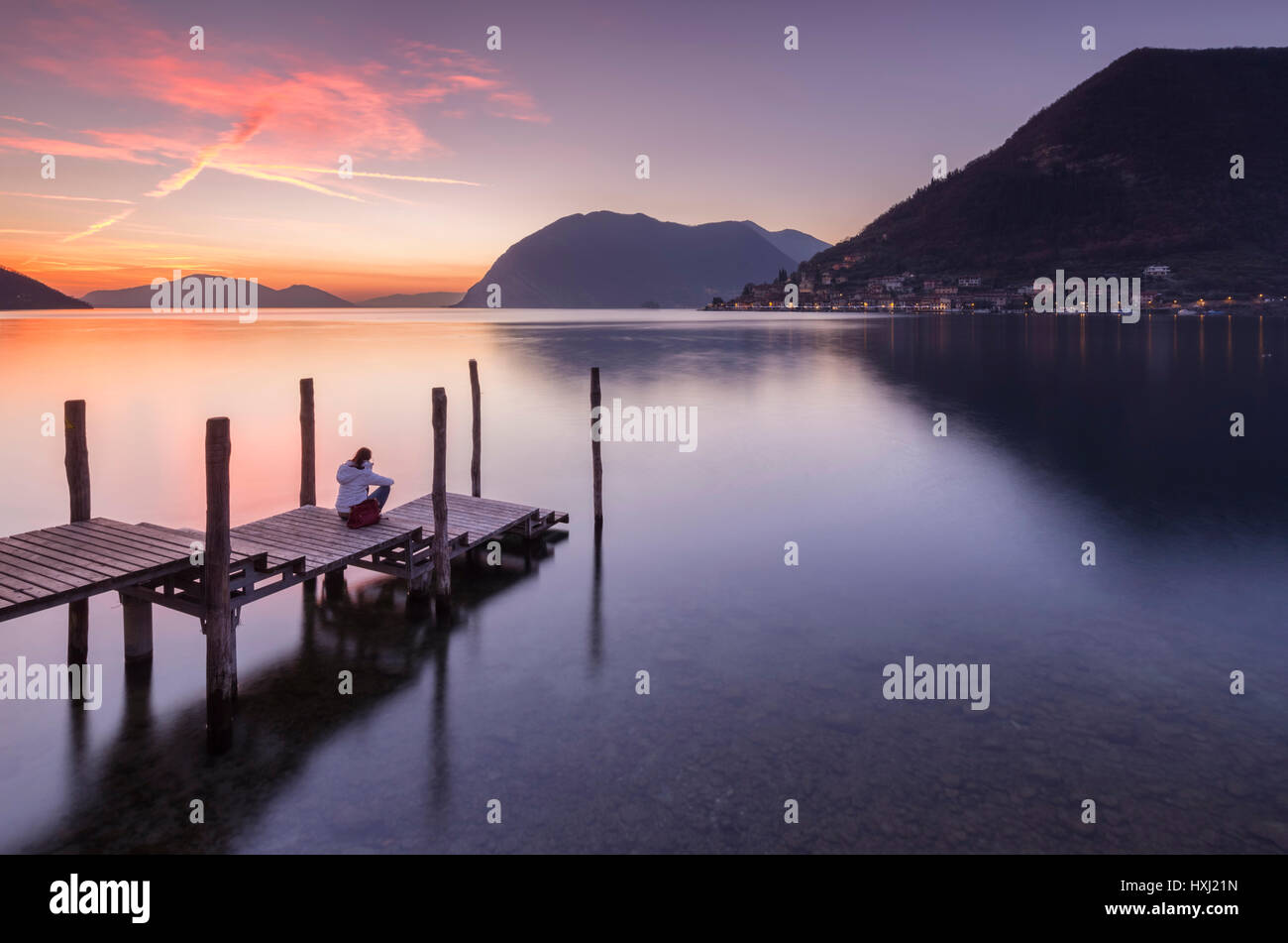 A girl on the pier of Sulzano during a winter sunset, Brescia Province, Iseo Lake, Lombardy, Italy. - Stock Image