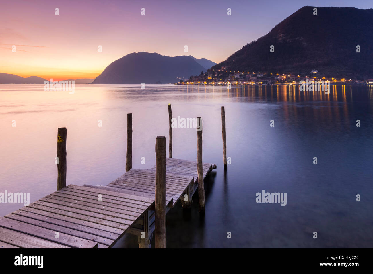 A pier in Sulzano, in front of Montisola and Peschiera Maraglio town during a winter sunset, Brescia Province, Iseo - Stock Image