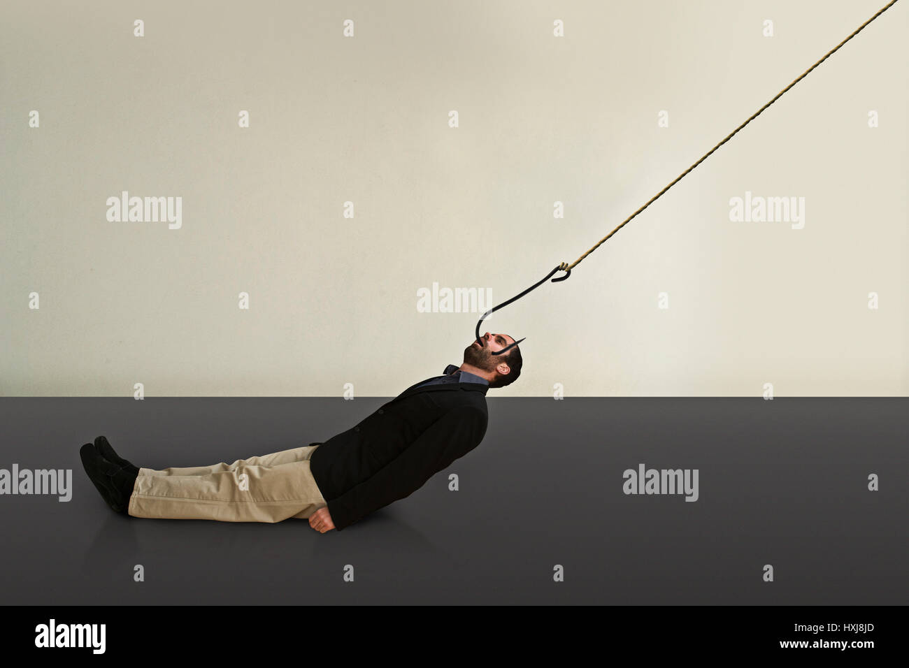 A hooked business man is dragged somewhere. - Stock Image