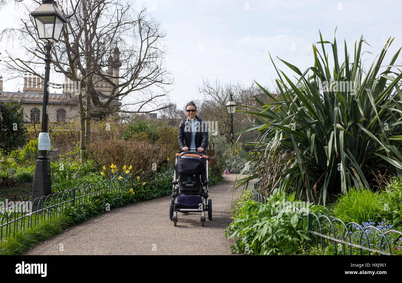 Brighton, UK. 28th Mar, 2017. A young woman with her baby walks through Pavilion Gardens in Brighton as the warm - Stock Image