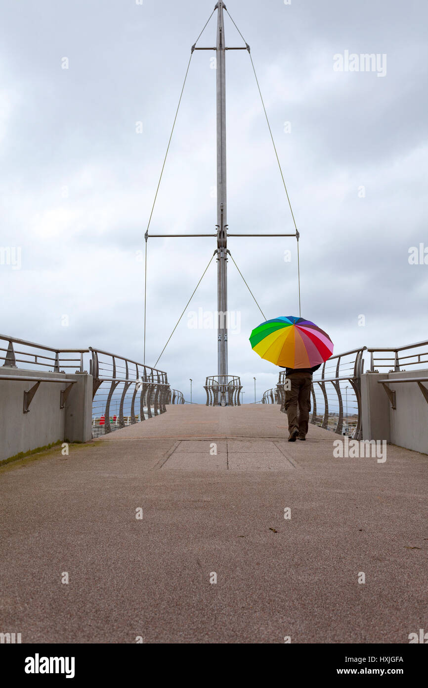 Lone male walking along the coastal path over the modern draw bridge at Rhyl North Wales holding a multicoloured - Stock Image