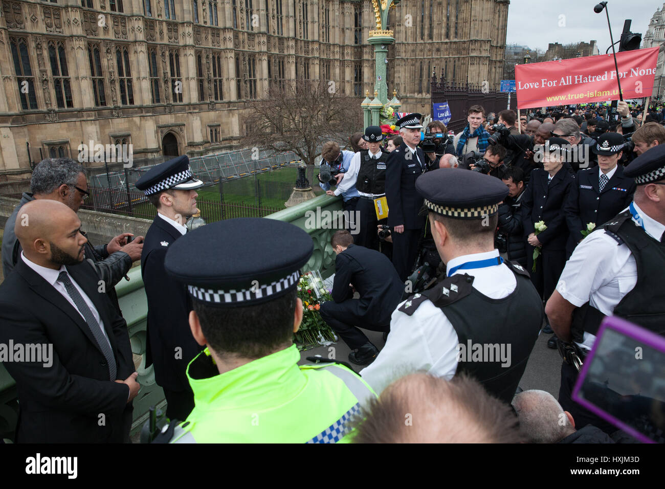 London, UK. 29th March, 2017. Metropolitan Police officers pay tribute on Westminster Bridge to the victims of last - Stock Image