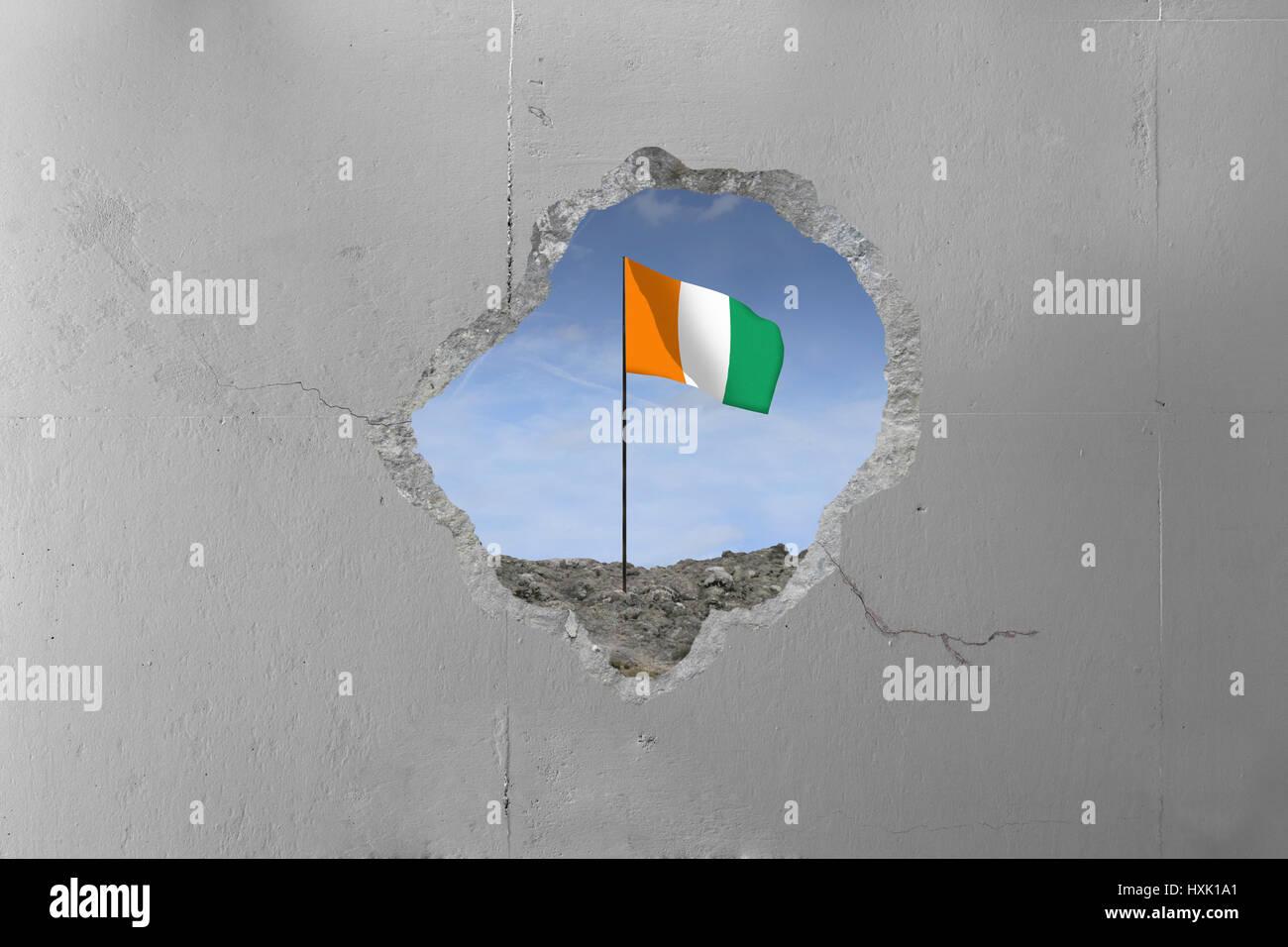 Cote d'Ivoire flag behind a concrete wall. - Stock Image