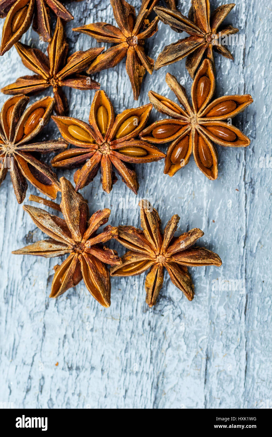 Old, wooden background and star anise seeds - Stock Image