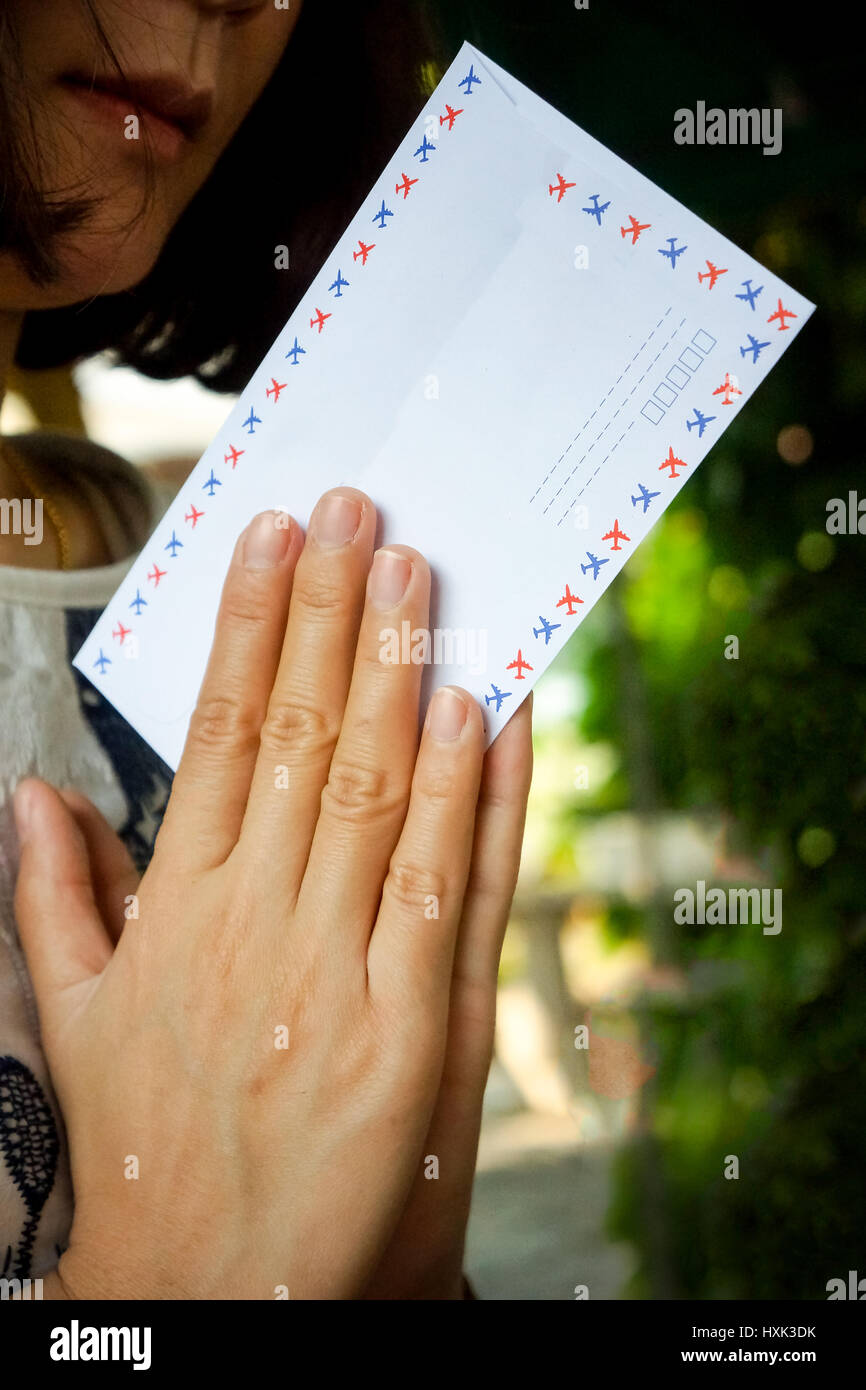 Asian woman praying with white envelope adn money within - Stock Image