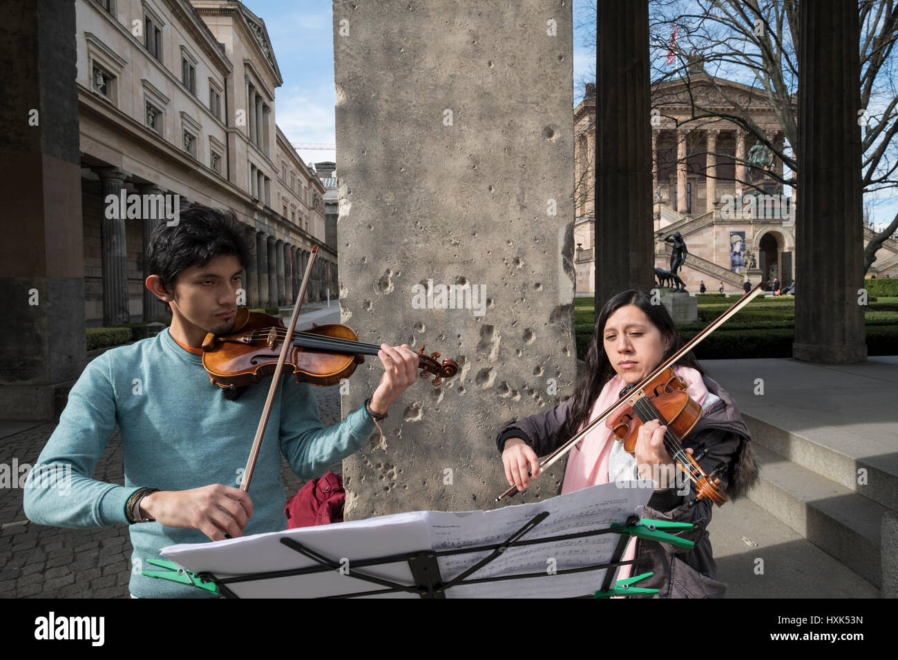Buskers playing outside Neues Museum with WWII bullet holes in column behind, Berlin, Germany. - Stock Image