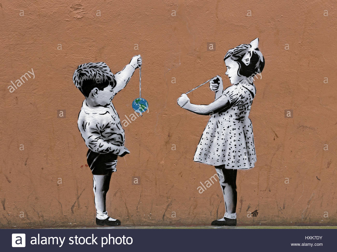 A piece of street art by JPS in Weston-super-Mare, UK shows two children playing conkers with one of the conkers - Stock Image