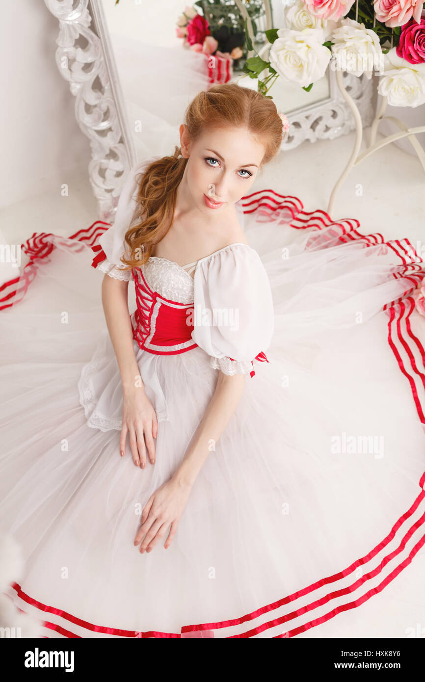 4ccf8698c4df Pretty ballerina in stage costumes and bouquets of spring flowers. Retro  dress. She sits on the floor. High angle shooting