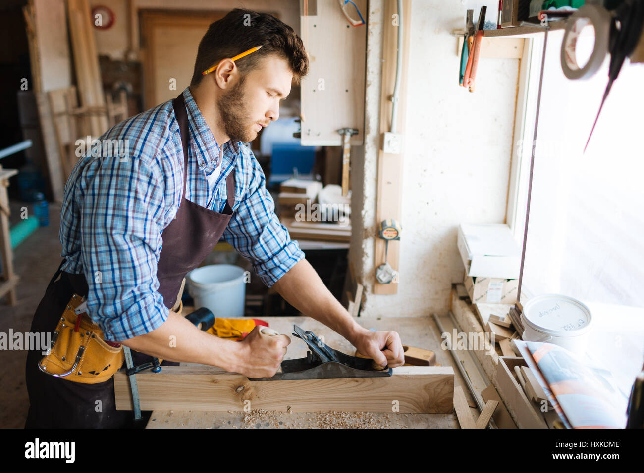 Concentrated woodworker in workshop - Stock Image