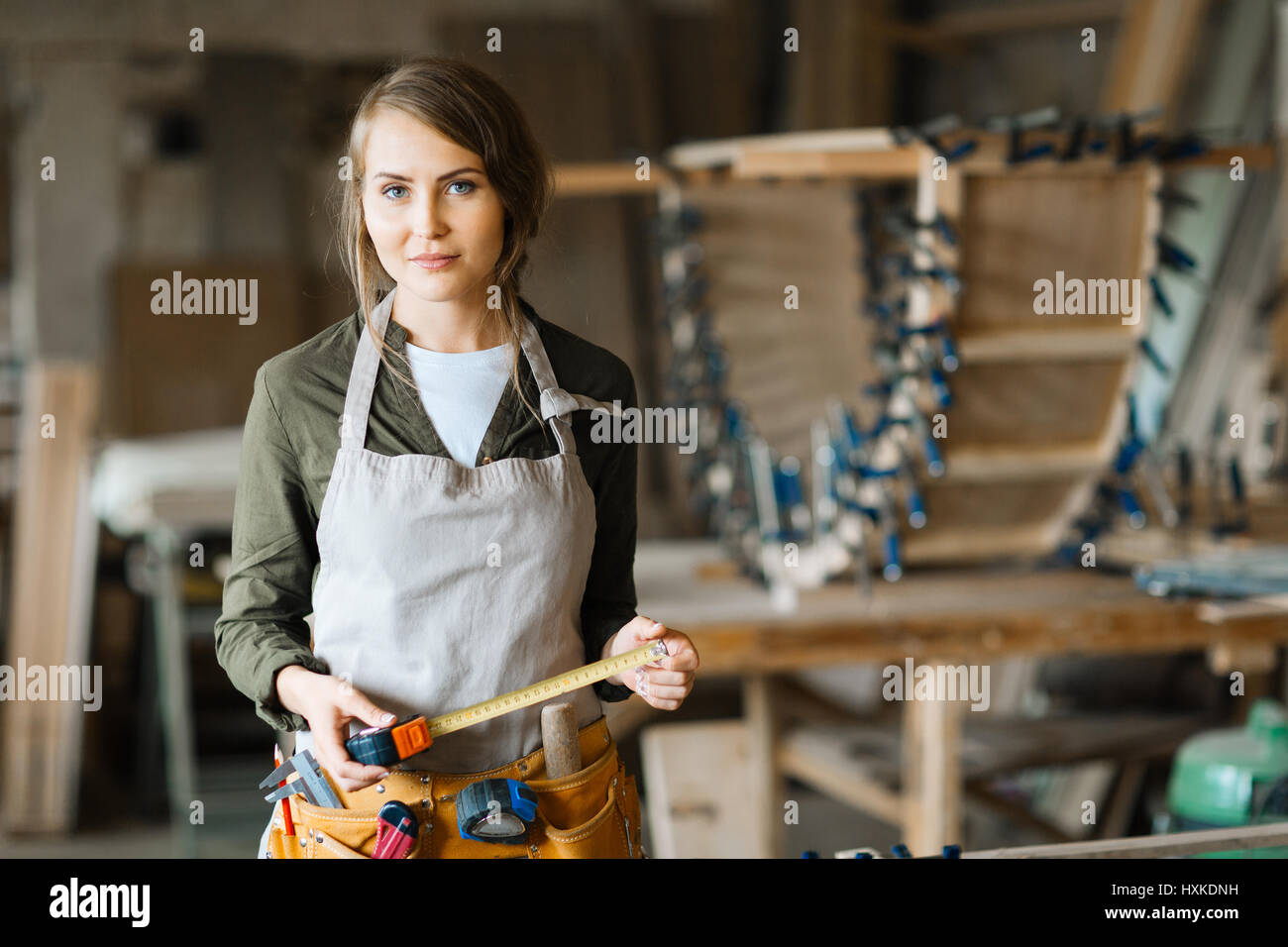 Fair-haired woodworker with tape measure - Stock Image