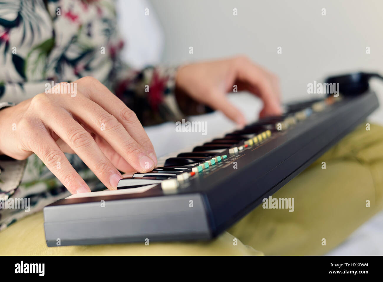 closeup of a young caucasian man playing a portable electronic keyboard - Stock Image