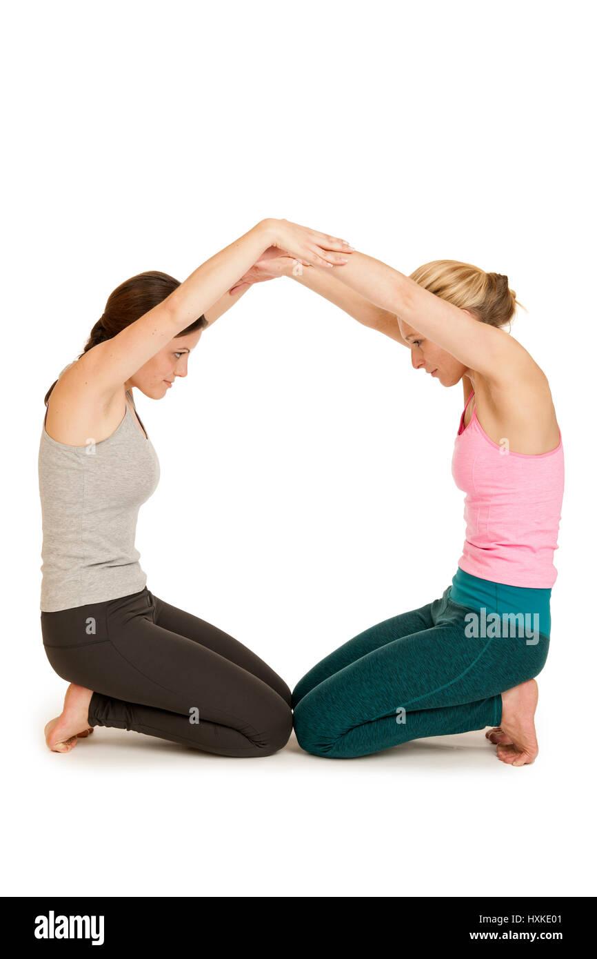 Ganzkörperansicht zwei junger Frauen im Sport-Dress bei der Darstellung des Buchstaben O auf weißen Hintergrund. - Stock Image