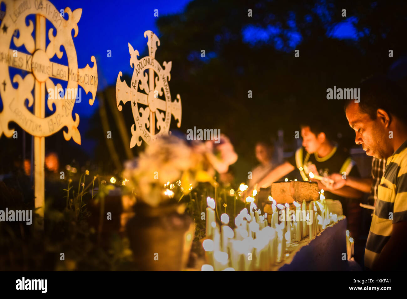 Pilgrims praying at the Cathedral Cemetery as a part of Semana Santa (Holy Week celebration) in Larantuka, Indonesia. - Stock Image