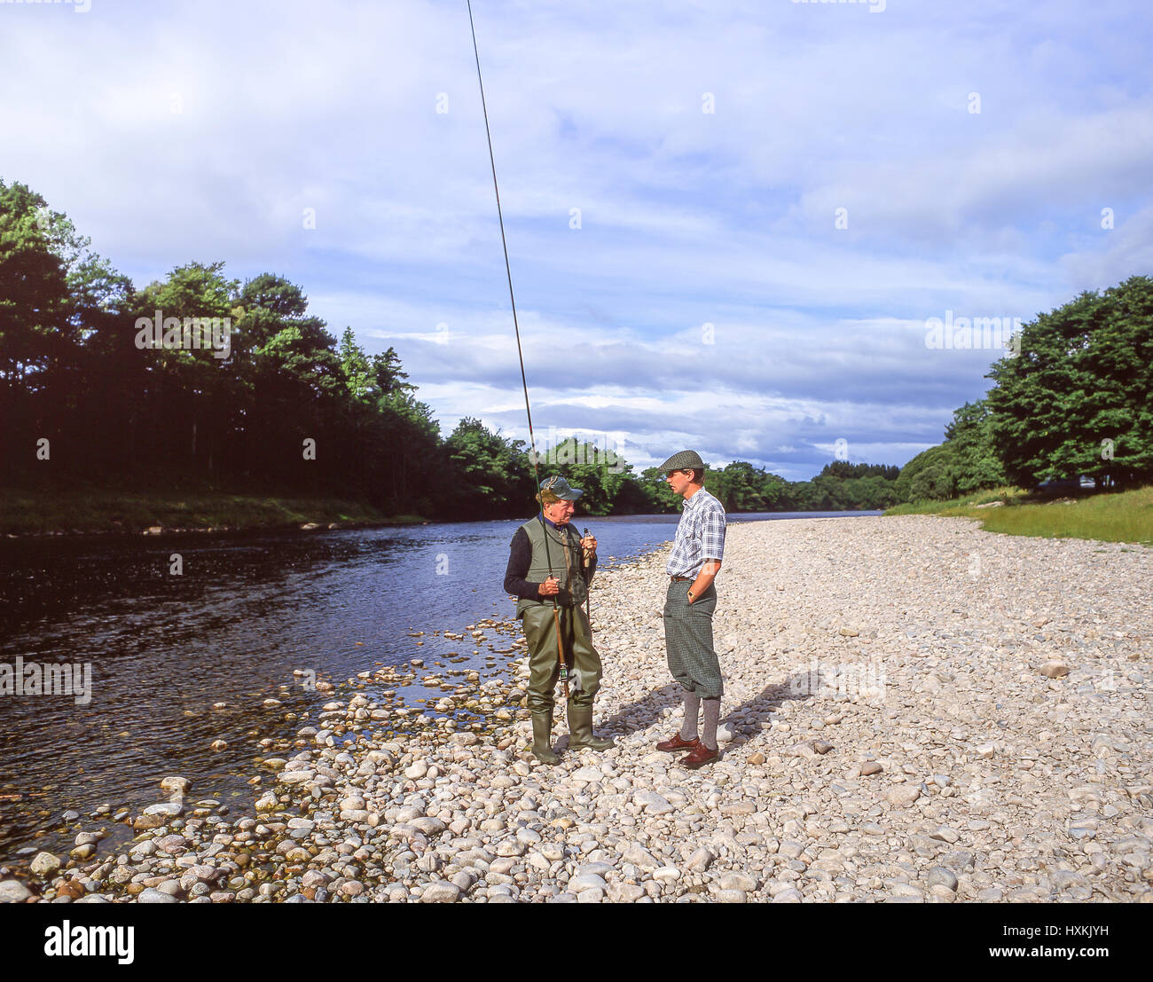 Salmon fisherman and Gillie on banks of River Dee, Aberdeenshire, Scotland, United Kingdom - Stock Image