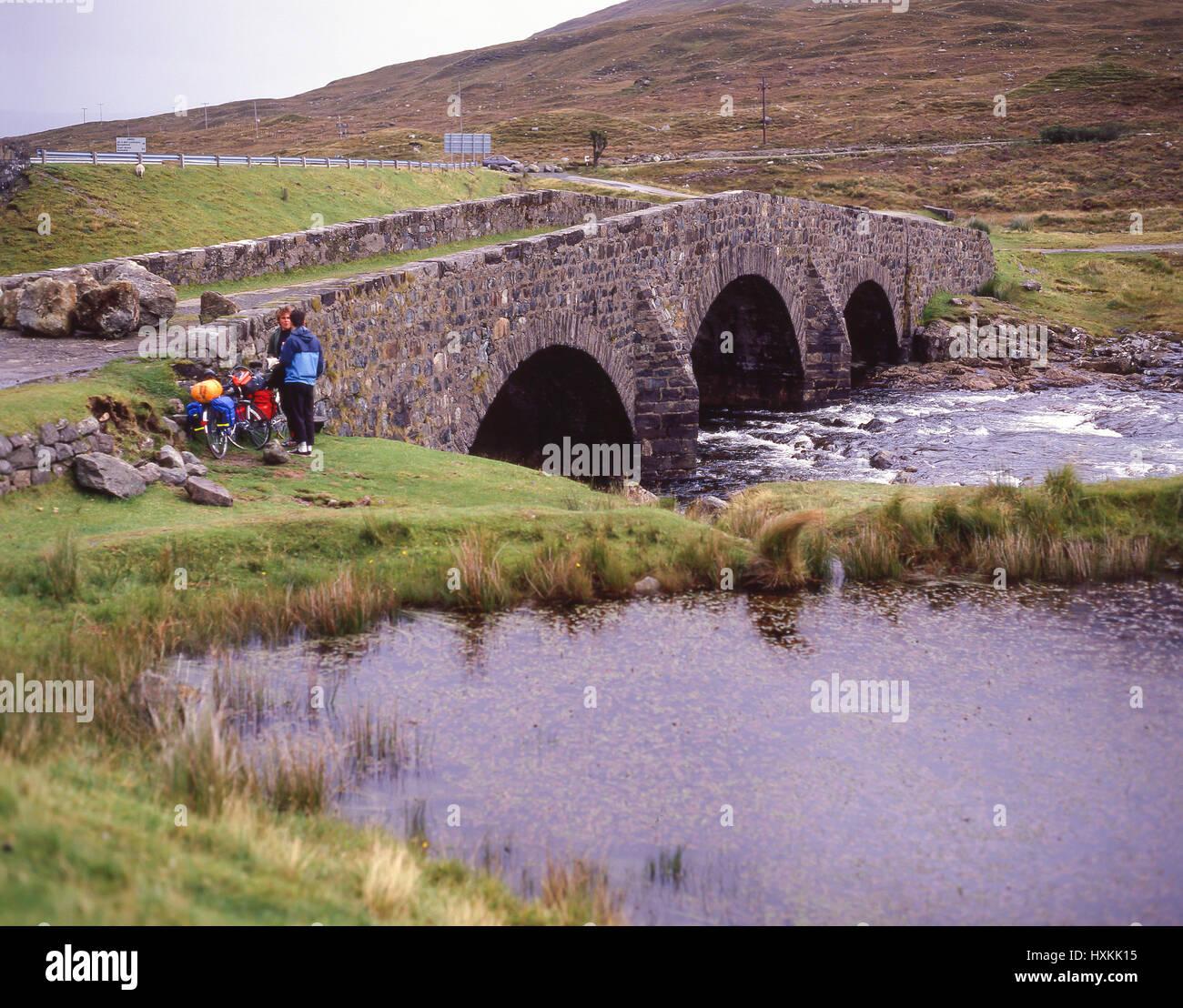 Cyclists by stone bridge, Isle of Skye, Inner Hebrides, Highland, Scotland, United Kingdom - Stock Image