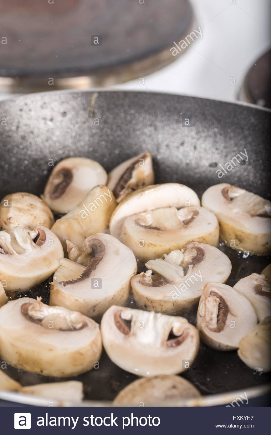 Frying sliced mushrooms in the frying pan - Stock Image
