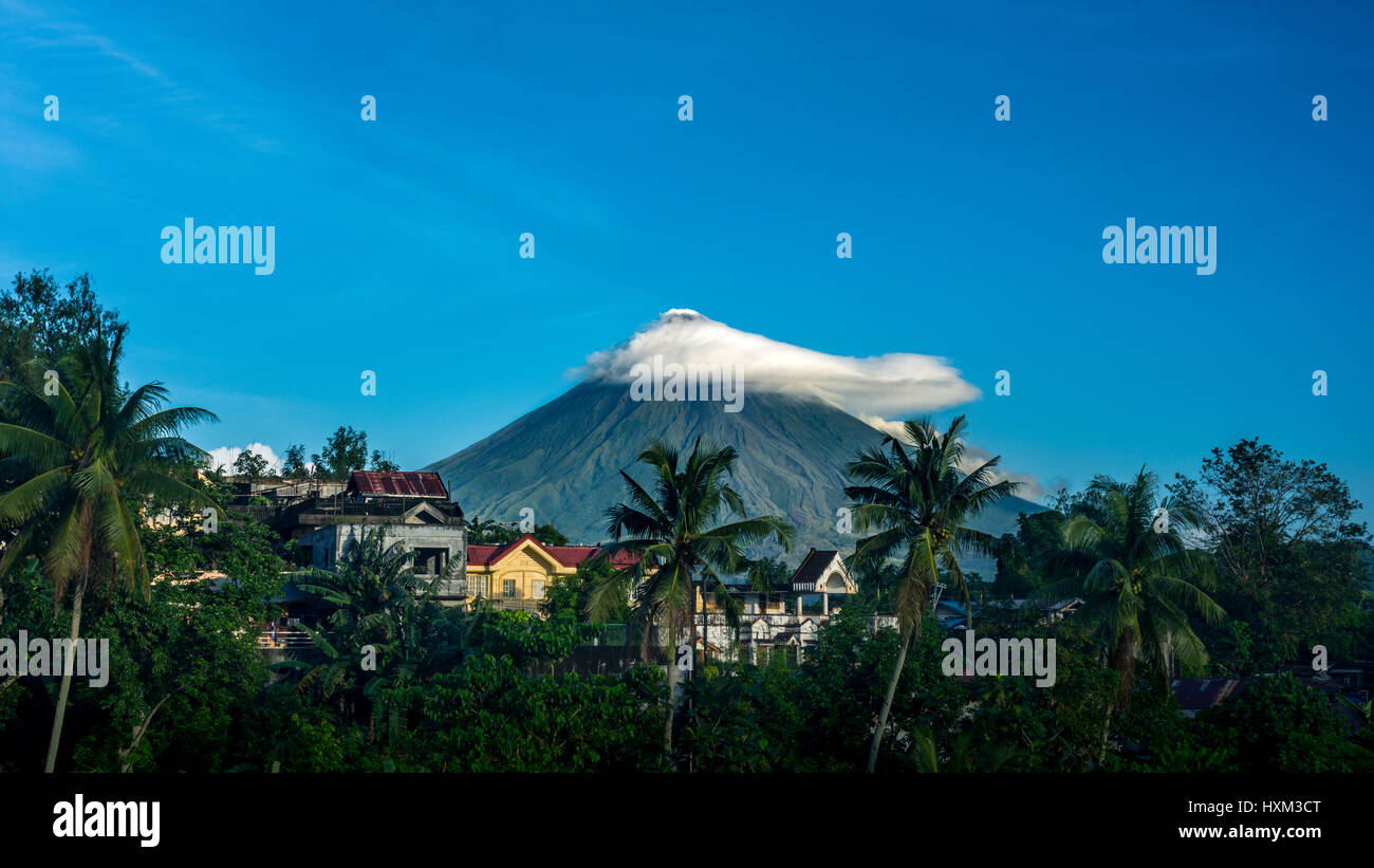 Distant view of Mayon Volcano, Legazpi, Philippines with small cloud cover with  houses and palm trees in the fore - Stock Image