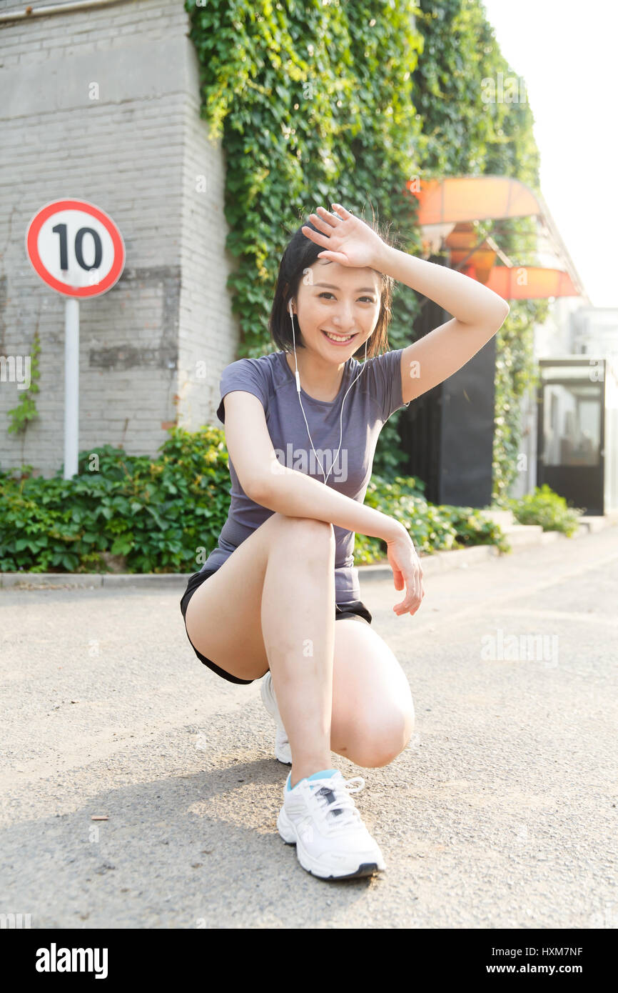 Young woman squatting with one knee down - Stock Image