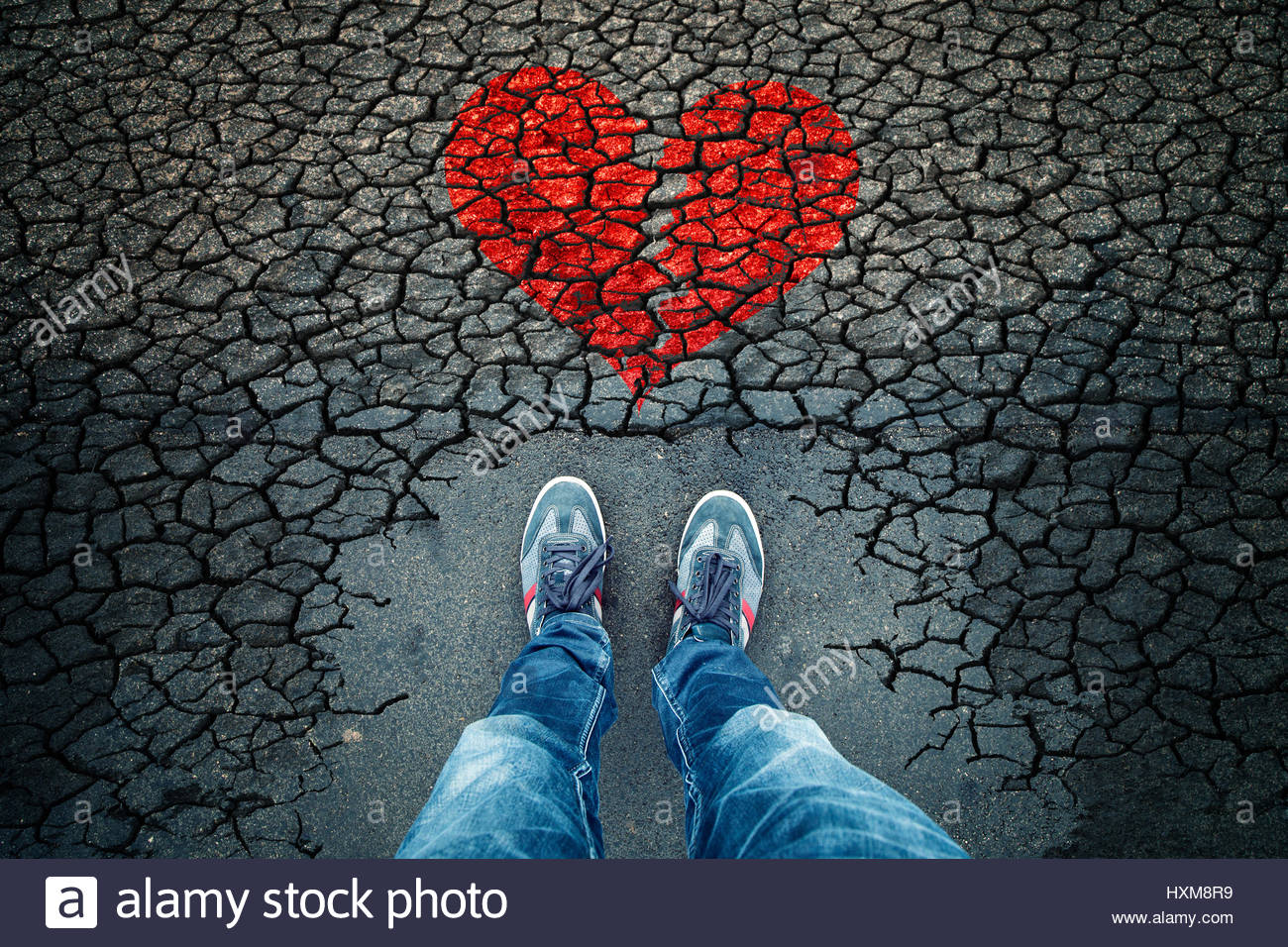 Lonely man standing on cracked asphalt floor with illustrated cracked broken heart symbol. Point of view perspective - Stock Image