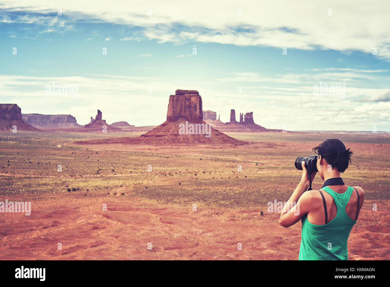 Vintage toned picture of female fit photographer takes pictures of buttes in the Monument Valley, USA. - Stock Image