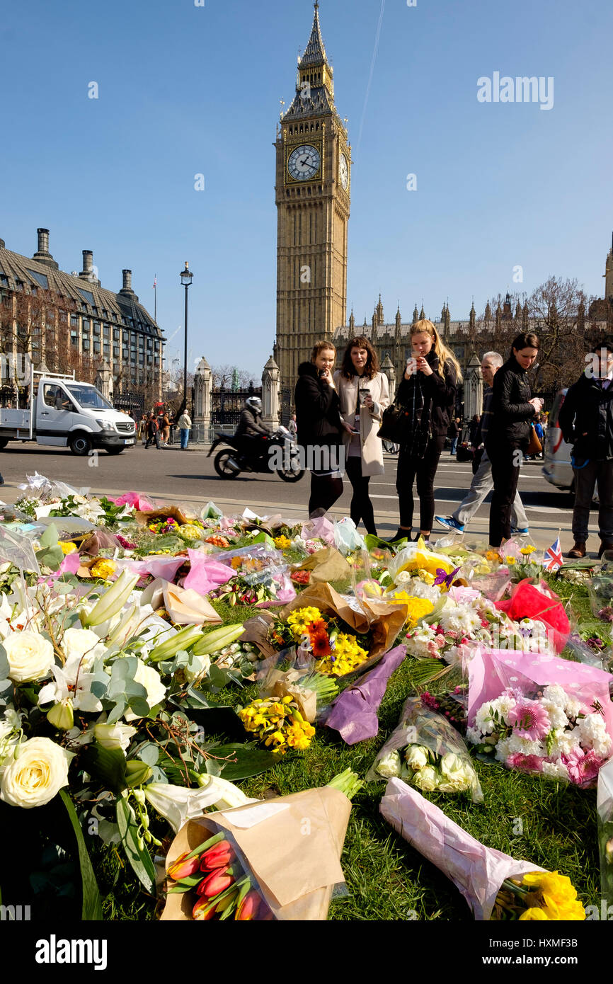 Westminster, London, UK. 27rd Mar, 2017. Young people contemplate the floral tributes left in Parliament Square - Stock Image