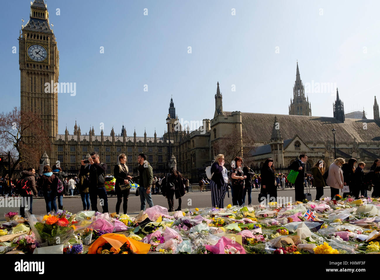 Westminster, London, UK. 27rd Mar, 2017. People contemplate the floral tributes left in Parliament Square to remember - Stock Image