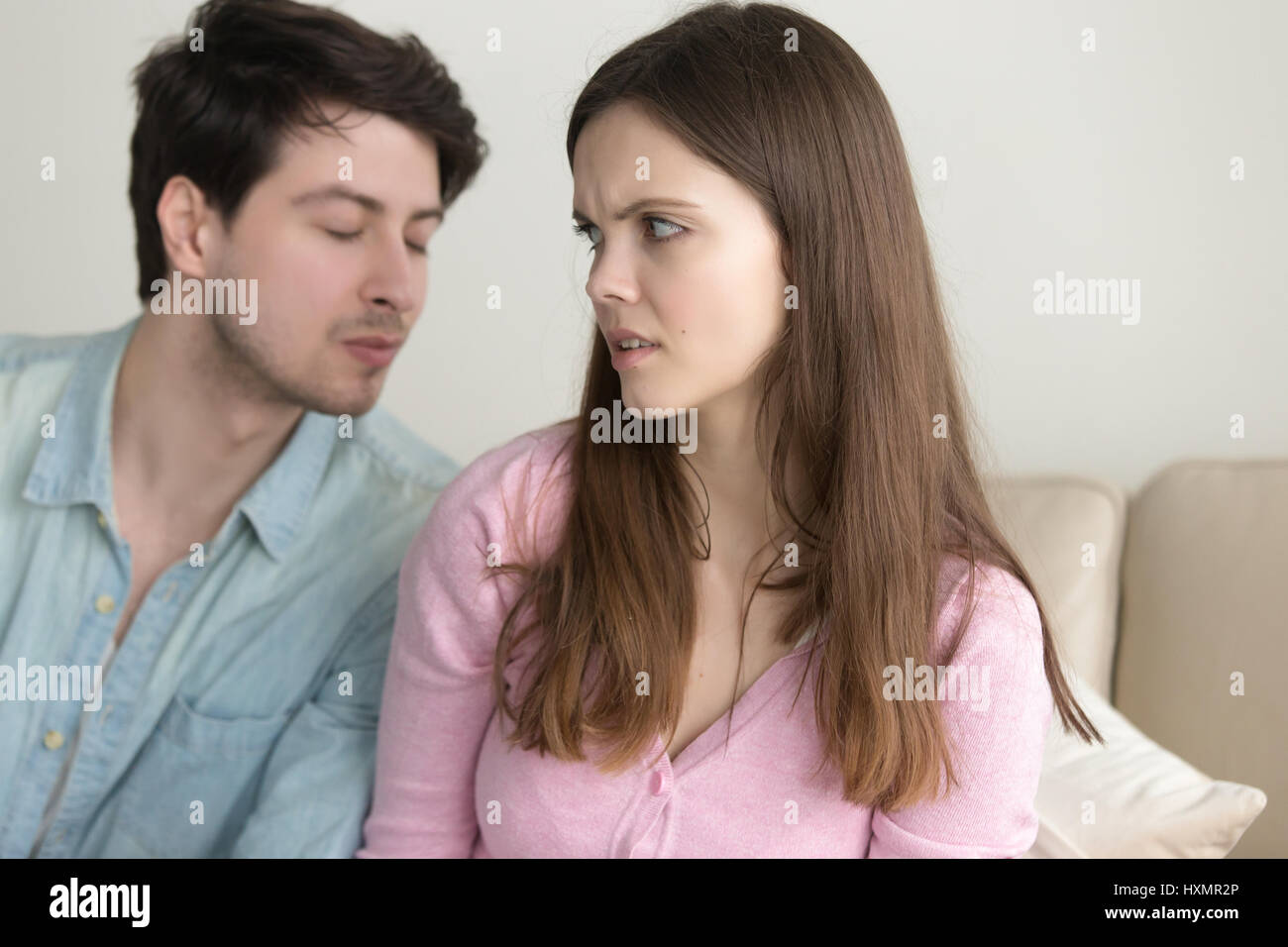 Man trying to kiss woman, she rejecting him, friend zone - Stock Image