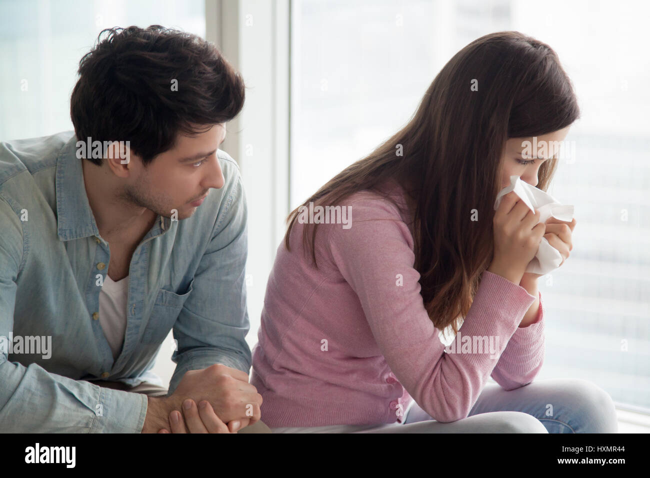 Man comforting upset woman crying, guy consoling weeping young l - Stock Image
