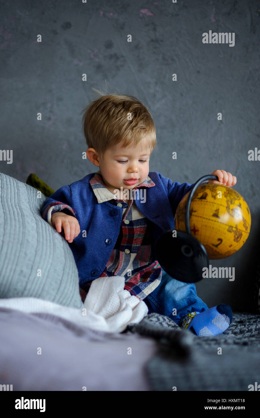 The pretty little boy examines the globe. The kid sits among big pillows and holds the yellow globe in hand. Stock Photo