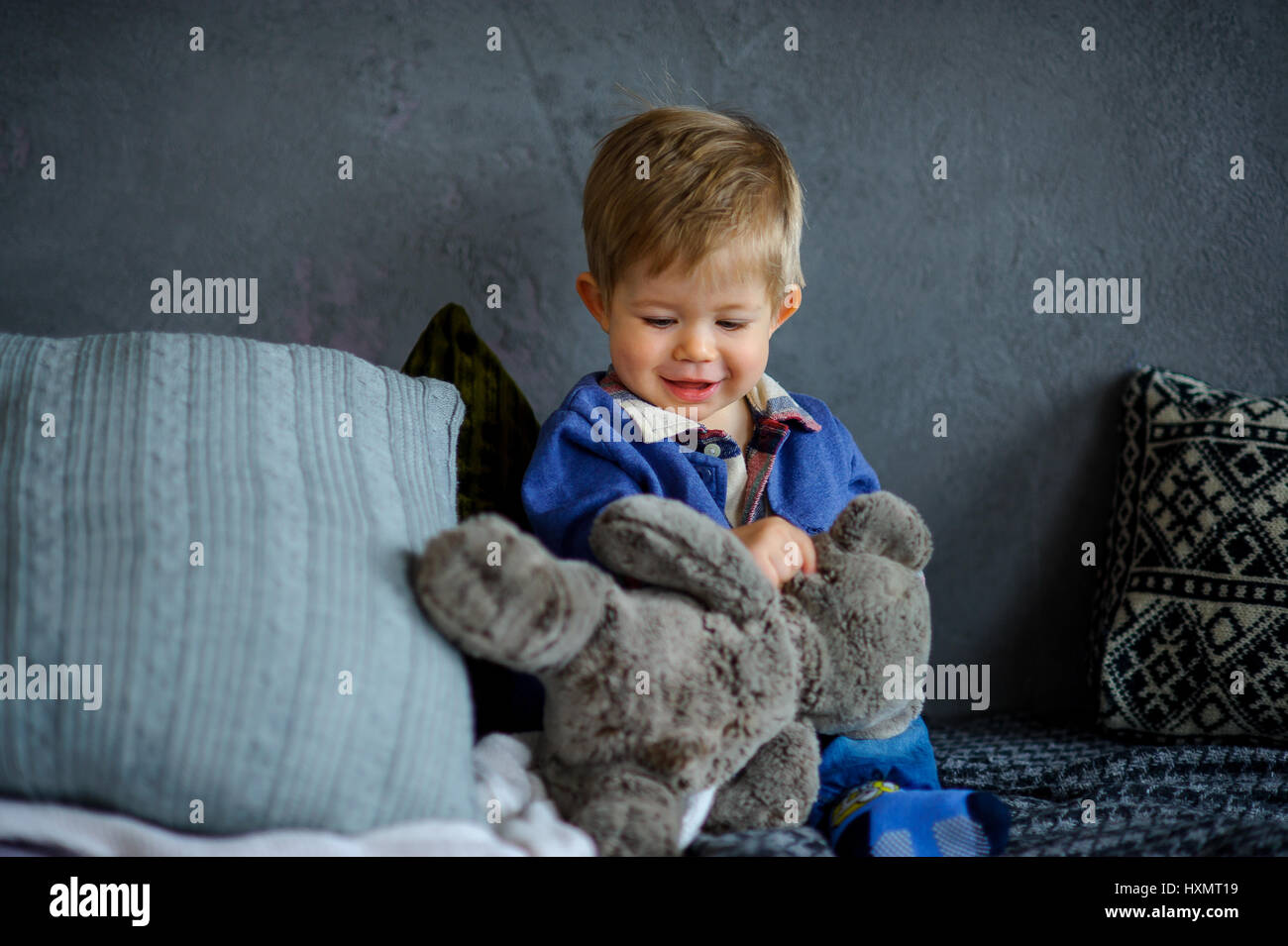 The charming kid plays with a teddy bear. The little boy sits among big pillows and holds with a hand a teddy bear. Stock Photo