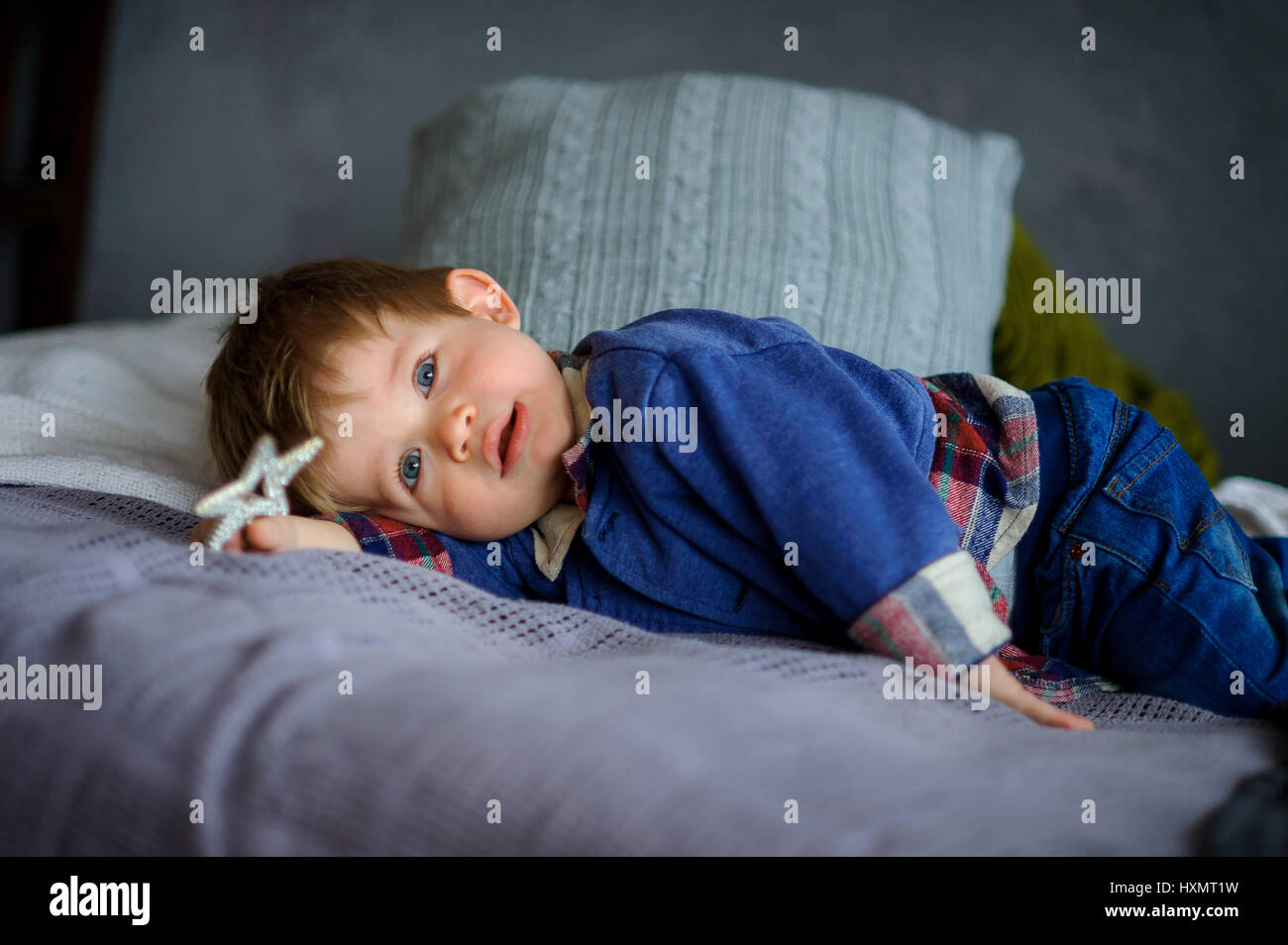 The little boy was tired of a game. The kid has lain down on a pillow. He is sleepy. In a hand a toy. Stock Photo