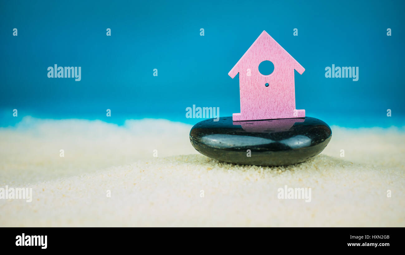 Symbol of little lilac house secured builed on black stone on blue background - Stock Image