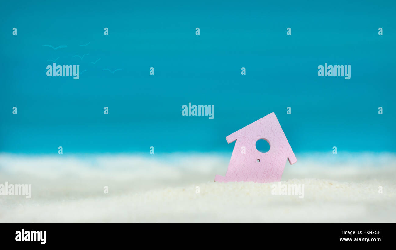 Symbol of little lilac house on the sand with bright blue painted sky background Stock Photo