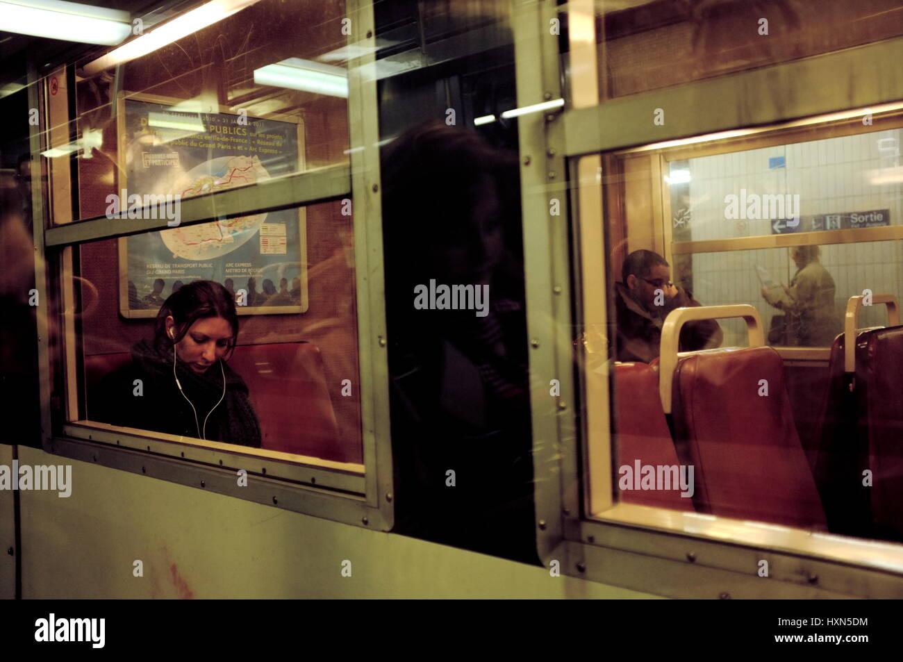 AJAXNETPHOTO. PARIS, FRANCE. - TRAVEL BY TRAIN - PASSENGERS ON A SUBURBAN TRAIN AT NIGHT. PHOTO:JONATHAN EASTLAND/AJAX Stock Photo