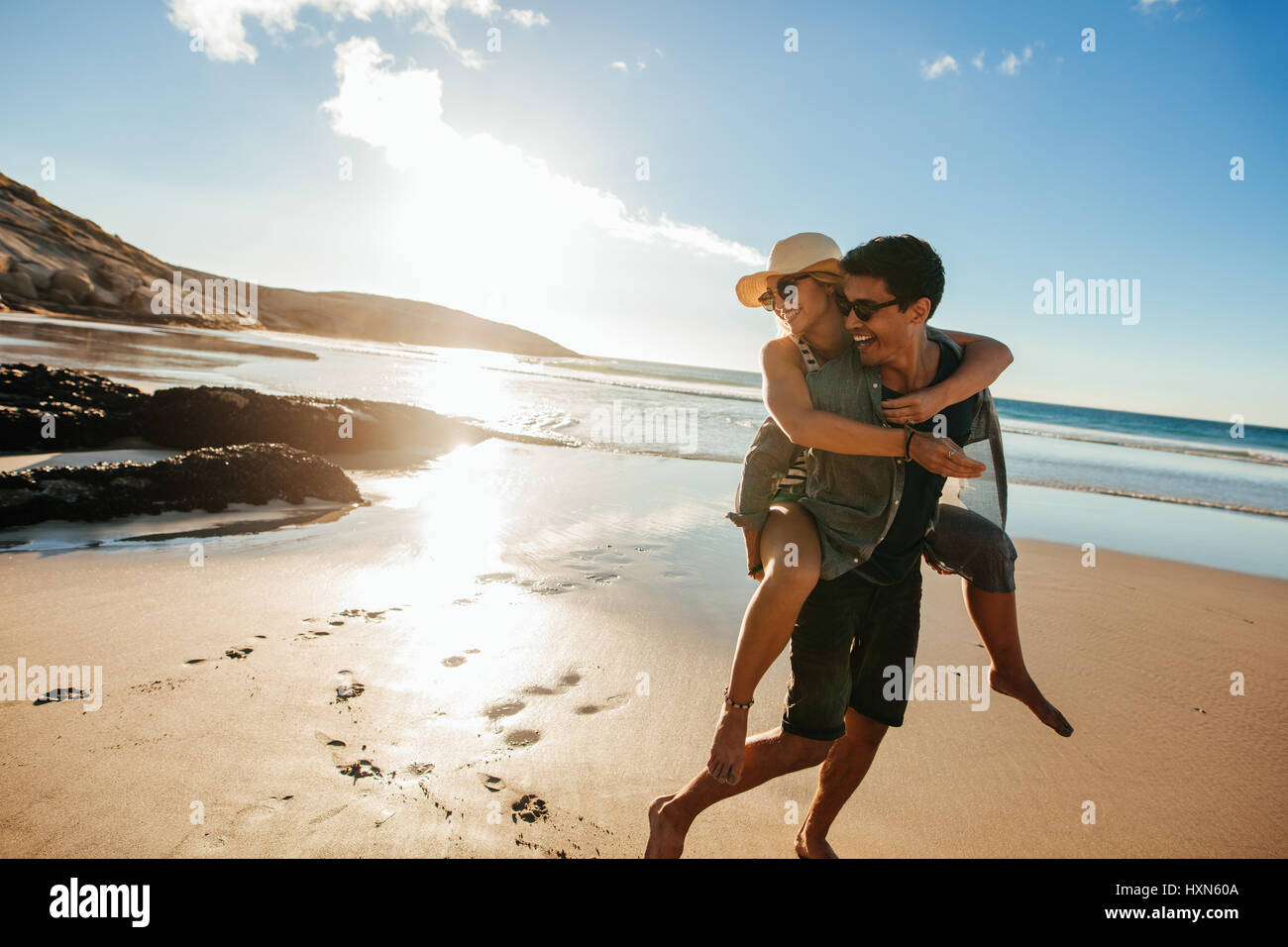 Romantic young couple enjoying summer holidays. Handsome young man giving piggyback ride to girlfriend on beach. - Stock Image