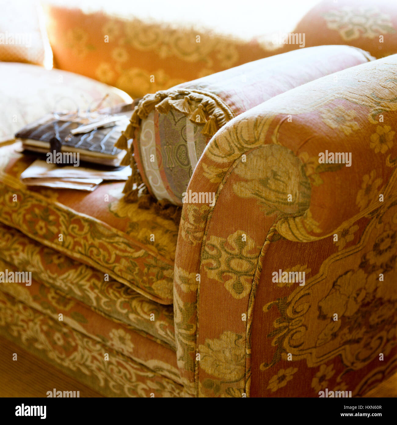 Cushion on floral patterned sofa. - Stock Image