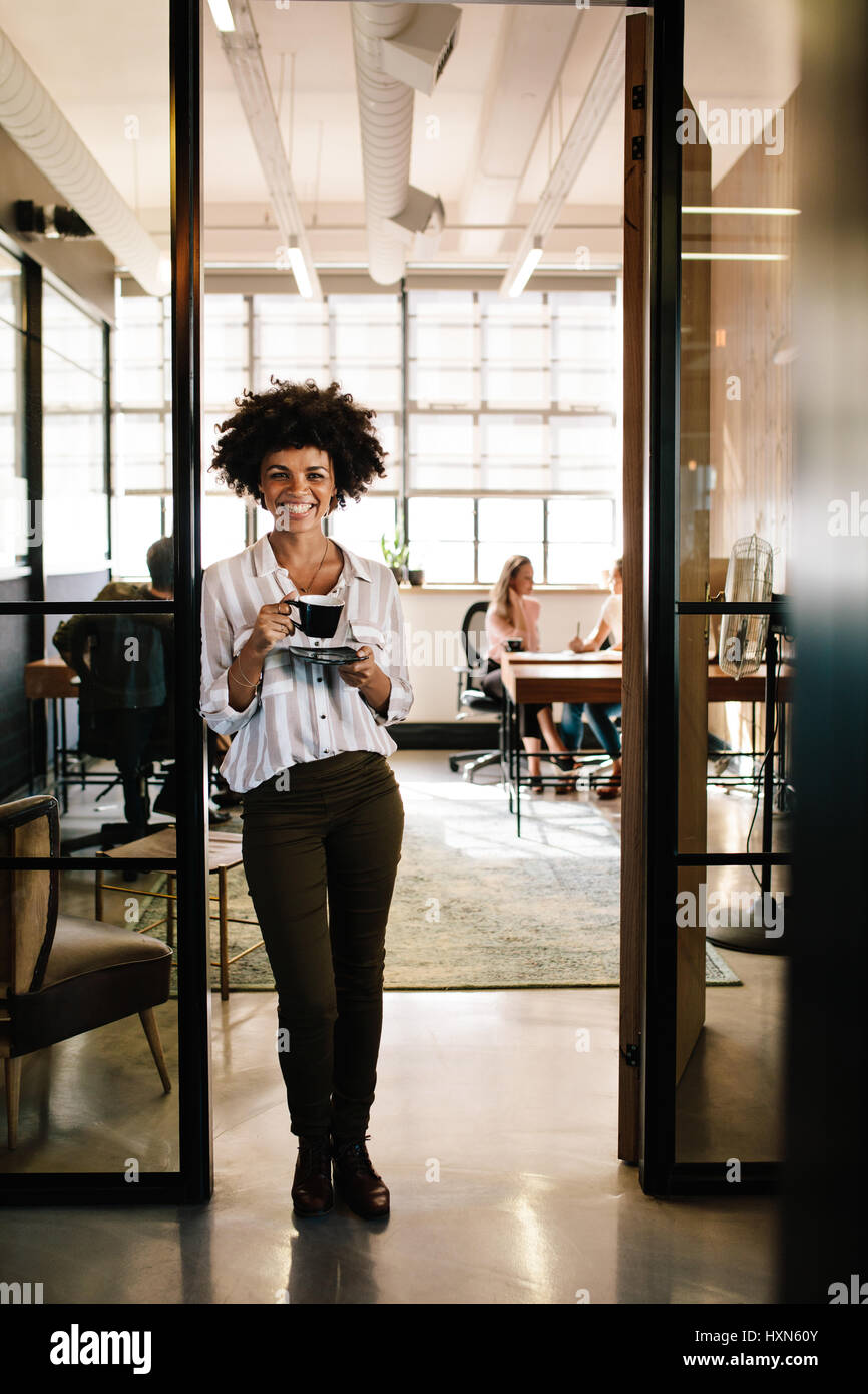Full length portrait of smiling young african woman standing in office doorway with coffee. Female having coffee - Stock Image
