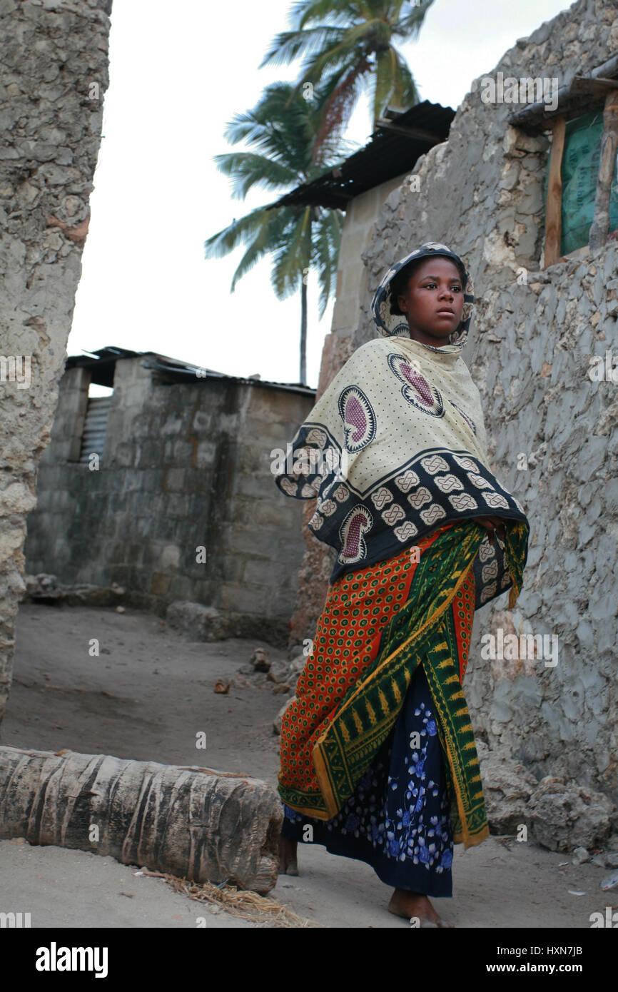 Zanzibar, Tanzania - February 20, 2008: Unknown barefoot dark-skinned African Muslim girl in head scarf, is on a - Stock Image