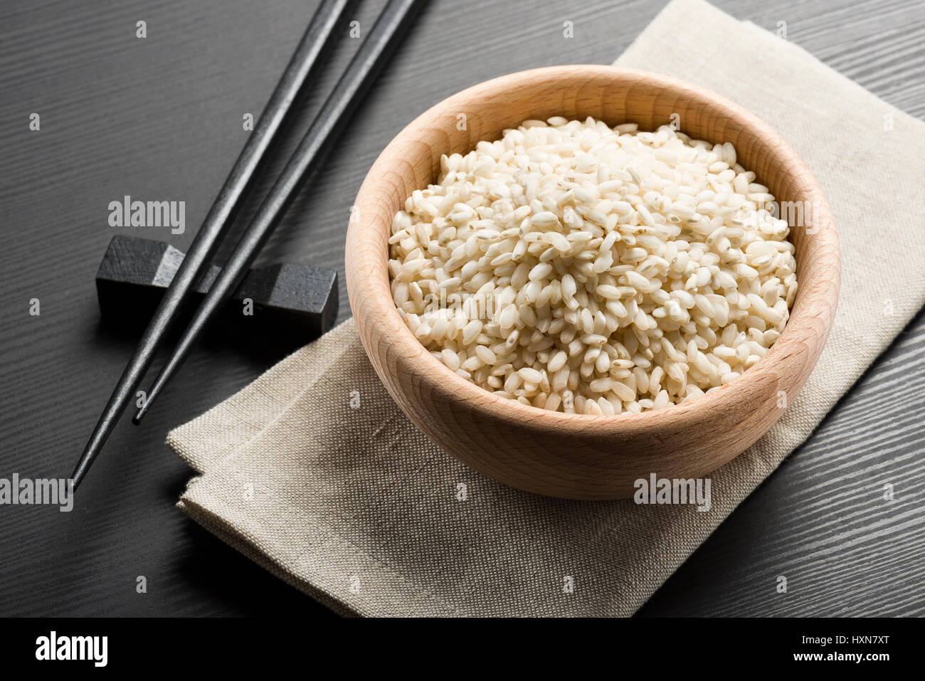 wooden bowl with rice and japanese chopsticks on black wooden table - Stock Image