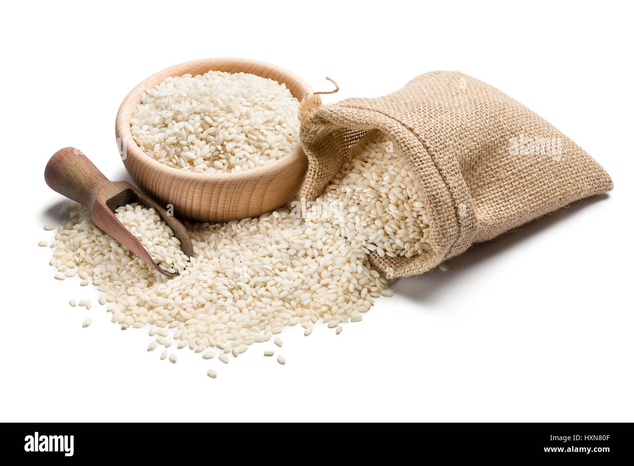 white rice in wooden bowl and juta bag on white background - Stock Image