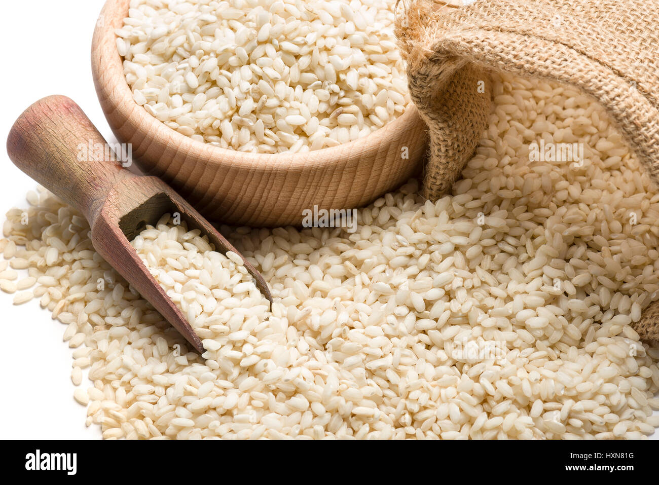 white rice in wooden bowl and juta bag closeup, on white background - Stock Image
