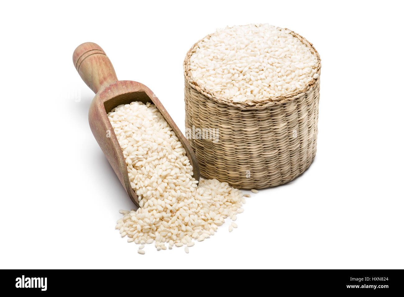 white rice in wooden scoopl and straw basket, on white background - Stock Image
