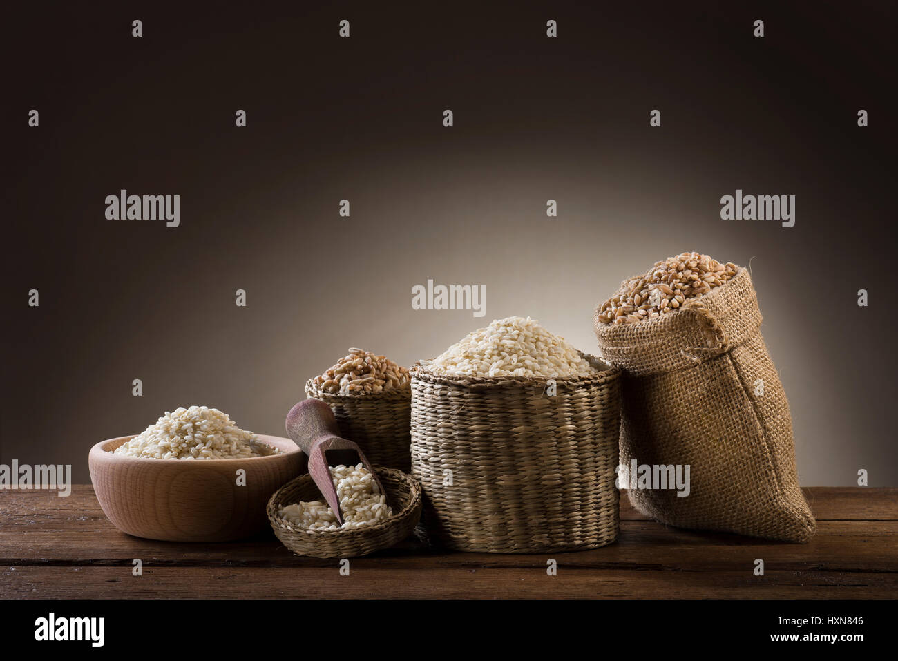 variety of different rice in rustic bowl and bags on wooden table - Stock Image