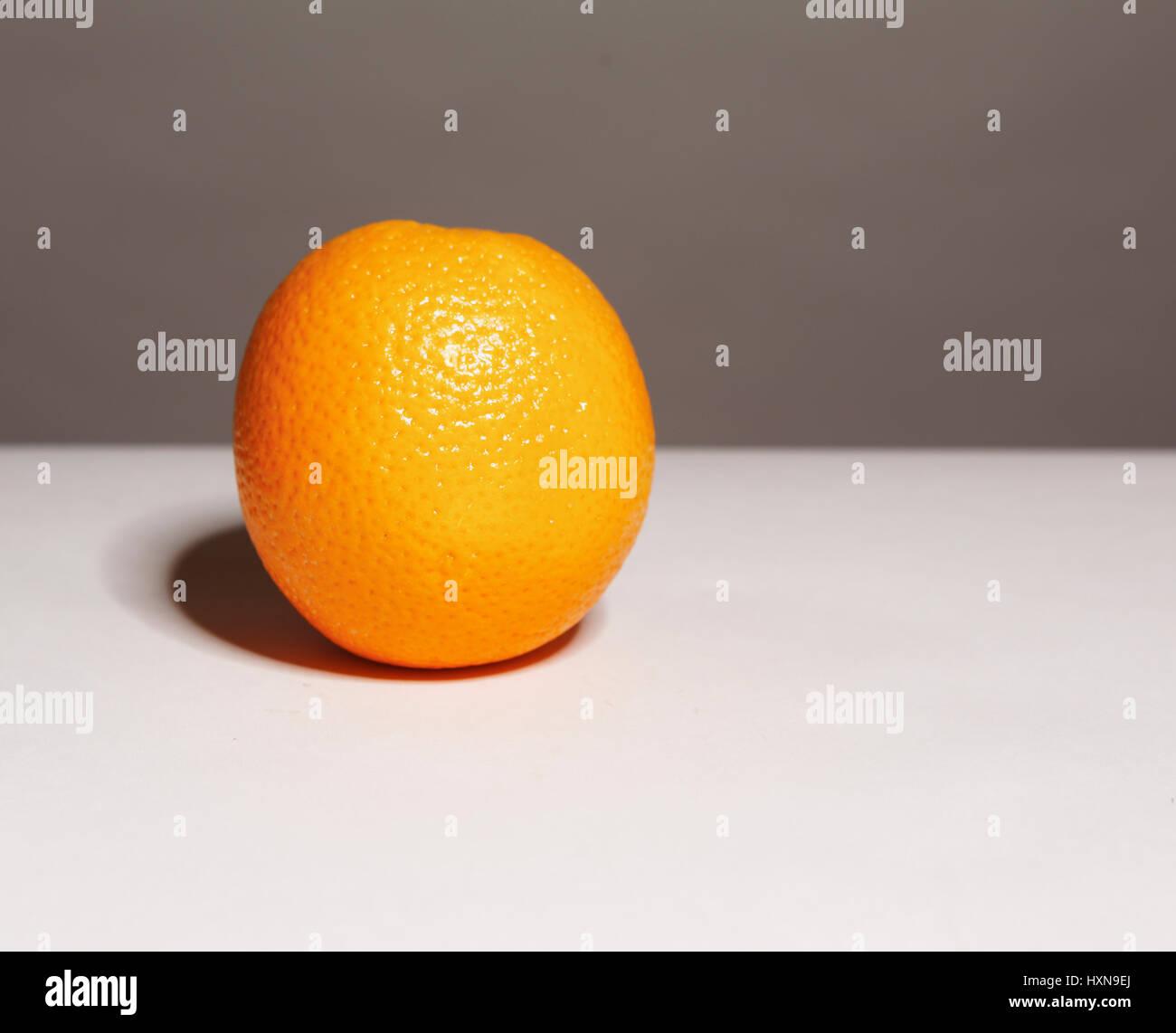 Single whole Orange shot on two tone grey background with shadow - Stock Image
