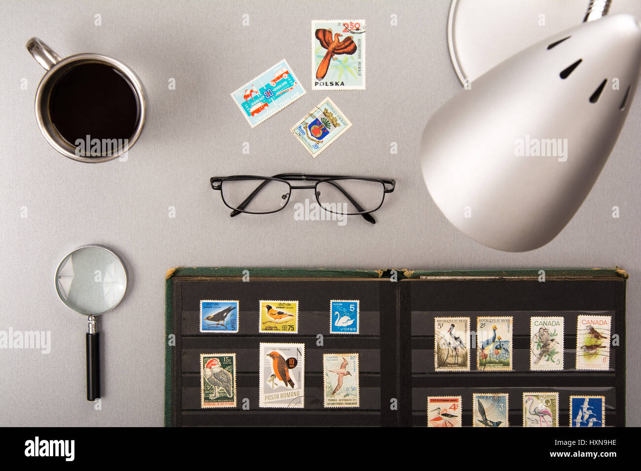 High angle view of a stamps collection with eyeglasses, a cup of coffee, a magnifier and a lamp - Stock Image