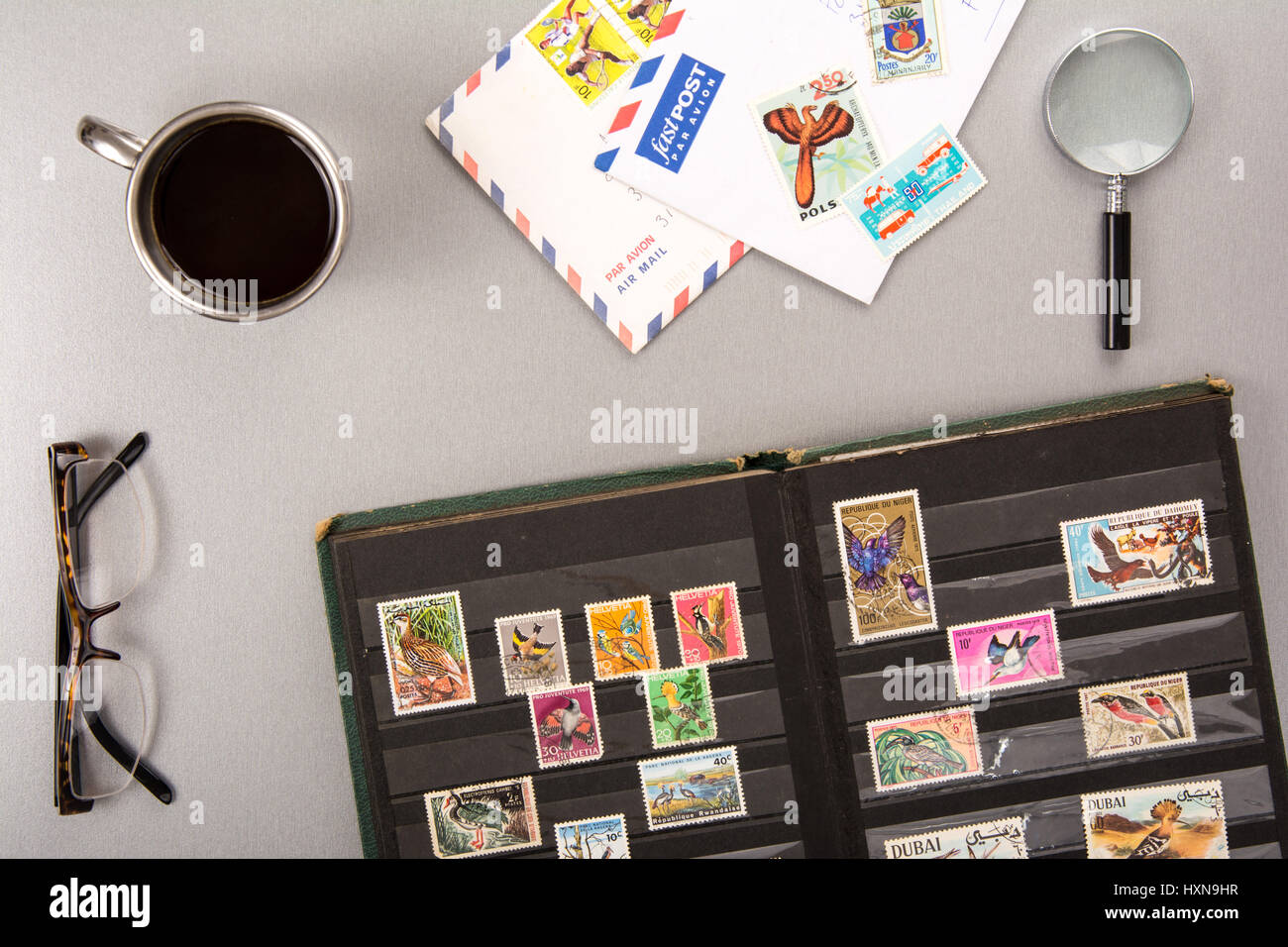 High angle view of a stamps collection with eyeglasses, a cup of coffee, a magnifier and letters - Stock Image