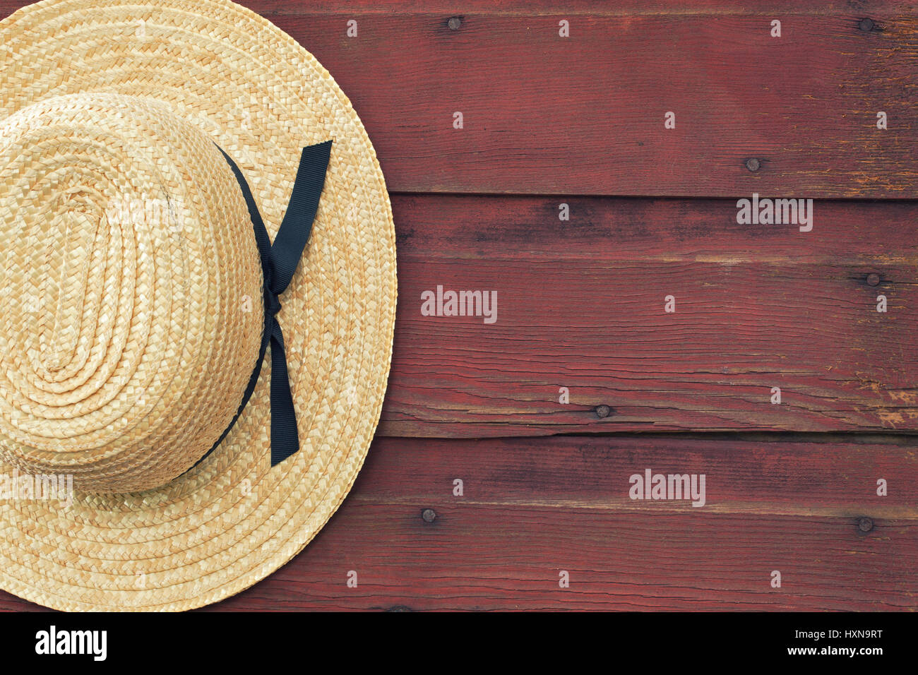 9e39de88 An Amish man's straw hat hangs on a red, wooden barn door - Stock Image